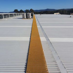 Fibre Reinforced Polyester (FRP) roof catwalk system in yellow creating a safe route across a corrugated roof