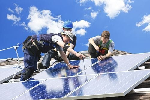 Group of people installing solar panels on rooftop