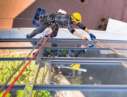 Person attached to safety harness working on the side of a building
