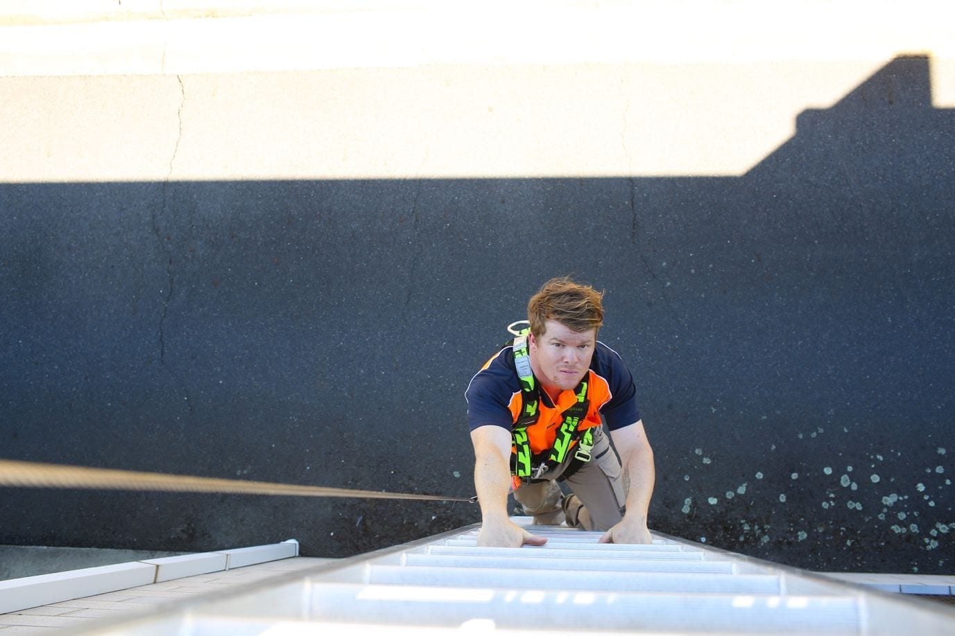 Person climbing rooftop access ladder system