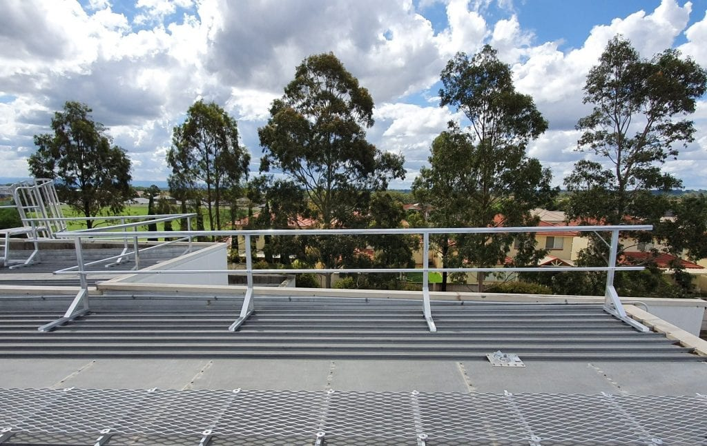 A rooftop guardrail system links up with a caged access ladder and walkway