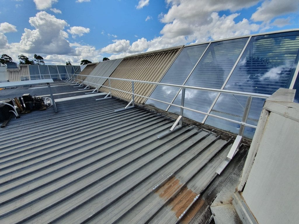 Guardrails preventing access to glass skylight panels on a shopping center roof-top