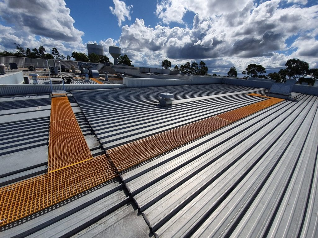 Yellow Fibre Reinforced Polyester walkway's providing safe routes for workers to access all areas of a large shopping center roof-top
