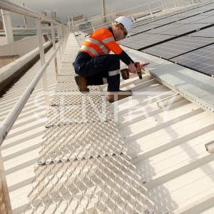 A worker installs rooftop solar panels protected from falls by an Aluminium Walkway