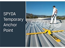 SPYDA temporary anchor point deployed on a corrugated metal roof with a worker attached by lanyard