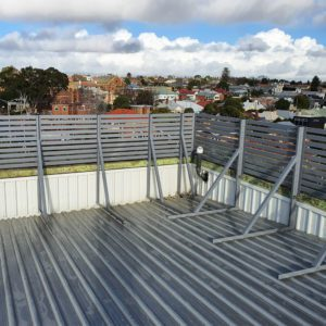 A powder coated slatted guardrail system which provides excellent safety for rooftop workers and looks great